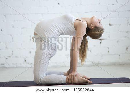 Pregnant Young Woman Doing Prenatal Yoga. Camel Pose