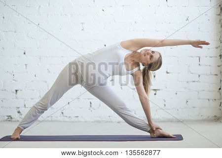 Pregnant Young Woman Doing Prenatal Yoga. Utthita Trikonasana Pose