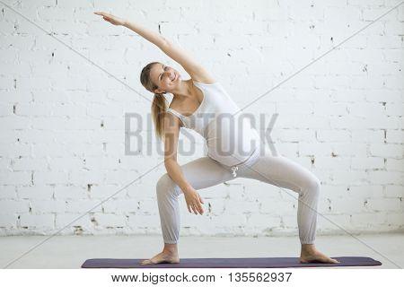 Pregnant Young Woman Doing Prenatal Yoga. Goddess Pose With Sidebend