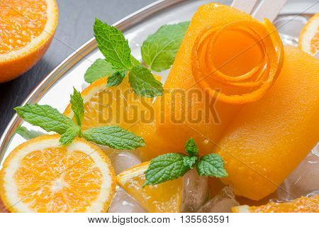 Orange sorbet ice cream decorated with a flower of orange peel mint leaves on silver plate with ice cubes orange pieces on black background. Orange sorbet ice cream popsicles. Horizontal. Close.