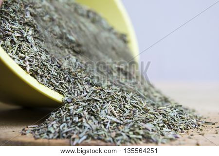 Mix of dried Provencal herbs pouring from a dish
