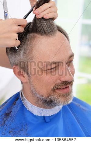 Man having a haircut  from female hairdresser at salon