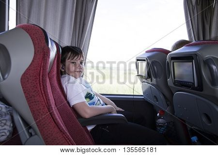 Teenager sitting in a tourist bus ,