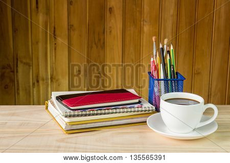 Note bookcoffee cupand stack of book on wooden table background