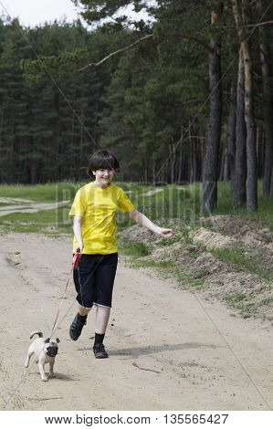 Boy walking with a dog near the forest on a summer day