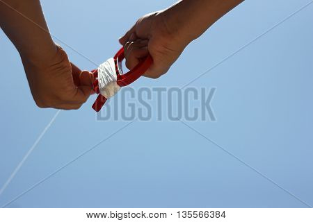 Boy flying a kite in a park with blue sky