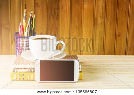 Smart phonecoffee cupand stack of book on wooden table background. Business concept