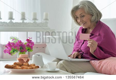 joyful Senior woman portrait with laptop and credit card