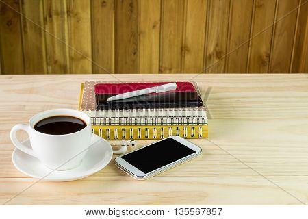 Cup of coffee with note book on wooden table background. Business concept