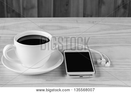 Smart phone and coffee on wooden table background.black and white tone