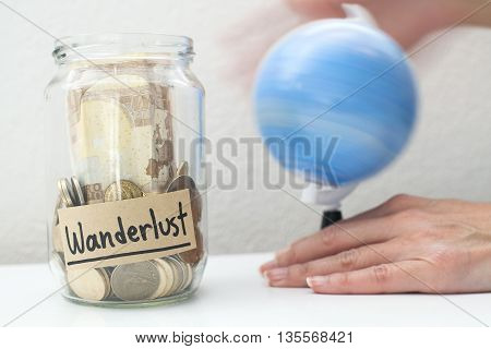 Saving up money to travel concept with money jar and hand rolling world map globe