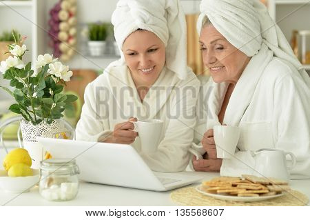Senior woman and  daughter  in a bathrobe with laptop and tea