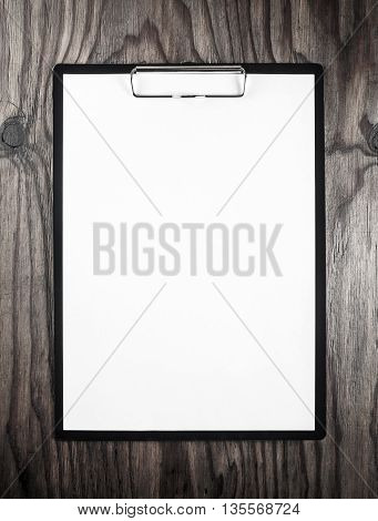 Blank letterhead. Blank sheet of paper in clipboard on dark wooden table background. Blank template for design portfolios. Mock-up for your design.