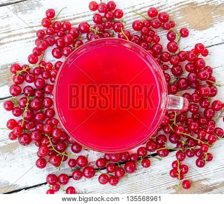 freshly squeezed red juice and bunches of red currants on a white wooden table with old paint. closeup