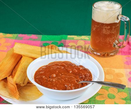 Chili in white bowl on white plate with hot tamales in corn husk sitting on colorful place mat and served with mug of beer with thick foamy head.