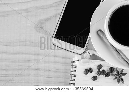 Coffee and open notebook with coffee beans on wooden table background. top view with copy space. black and white tone