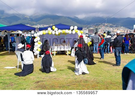 QUITO, ECUADOR - JULY 7, 2015: Nuns praying for pope Francisco, little altar in a tent with flowers and ballons in the middle of the grass.
