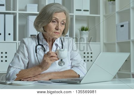Thoughtful senior doctor sitting at table with laptop in office with cup of coffee