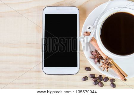 Smart phone and coffee with coffee beans on wooden table background