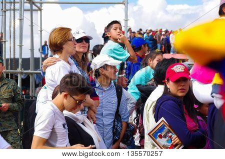 QUITO, ECUADOR - JULY 7, 2015: Adults, woman and men, paying attention to pope Francisco mass, sunny day.