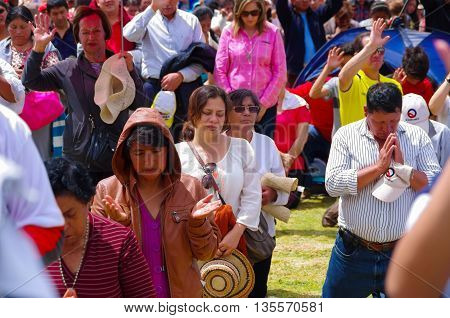 QUITO, ECUADOR - JULY 7, 2015: People meditating and praying in pope Francisco mass event, strong sun at midday.