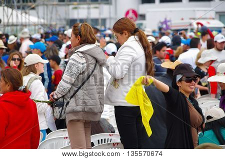 QUITO, ECUADOR - JULY 7, 2015: Women waitting to see pope Francisco mass event, one with her mobile phone and other with a yellow flag.