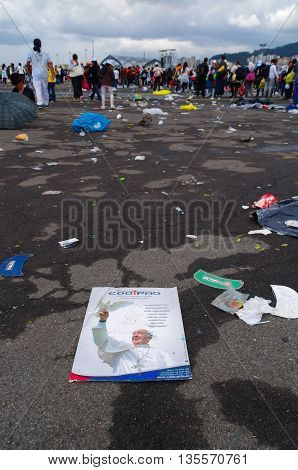 QUITO, ECUADOR - JULY 7, 2015: Pope Francisco poster on the floor after his mass on Quito, people very far walking to getting out.