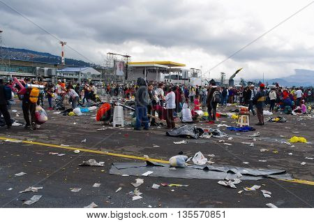 QUITO, ECUADOR - JULY 7, 2015: Huge place where pope Francisco mass event was, people still in the rain. Garbage on the floor,