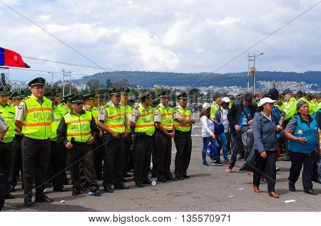 QUITO, ECUADOR - JULY 7, 2015: After the event, people getting out of the place and police guarding them untill the end.