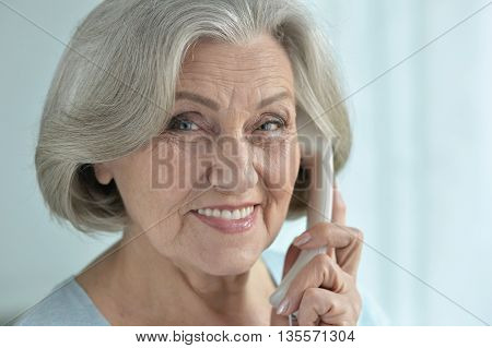 Portrait of a happy senior woman talking phone