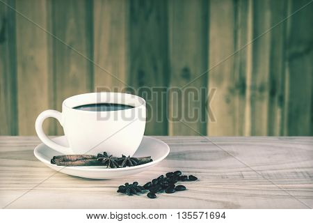 coffee cup and coffee beans on wooden table background. vintage tone