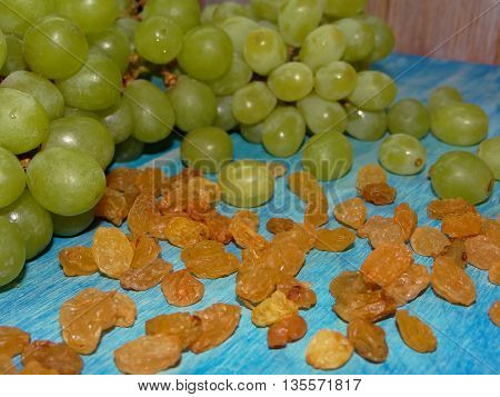 green grapes and raisins lying on blue wooden boards