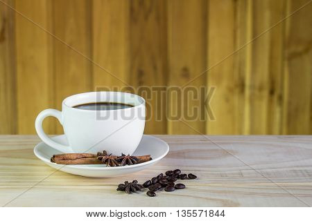 coffee cup and coffee beans on wooden table background.