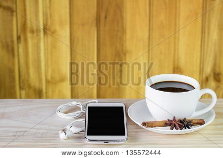 Smart phone and coffee on wooden table background