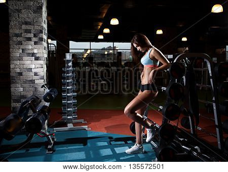 Beautiful sexy girl with perfect abdominal muscles at the gym. The concept of a healthy lifestyle and exercise. Strong woman. Feminism.