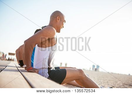 Men doing exercises outdoors on the beach.