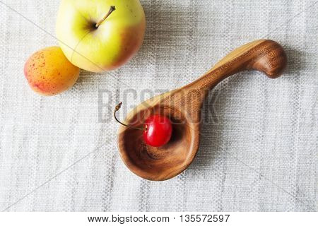 Composition of cup, wooden spoon and fruits. Fruits is the reason of the longevity. White retro, wooden spoon and fruits on a napkin on the table.