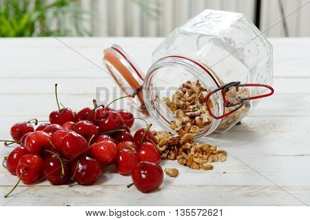 a glass jar with hulled nuts and cherries