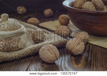 Walnuts in old wooden bowl. Selective focus