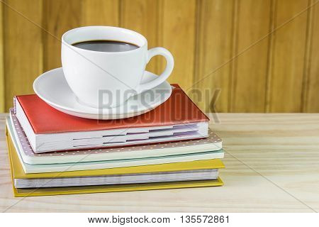 Cup of coffee and note book on wooden table background