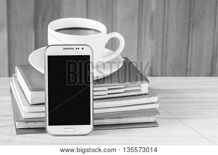Smart phone coffee and note book on wood table background. Business concept.black and white tone