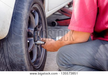 Close up shot of the hands of mechanics using pneumatic wrench to loosen the nut wheel of car