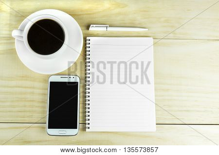 Smart phone coffee and book blank with pen on wood table background. top view