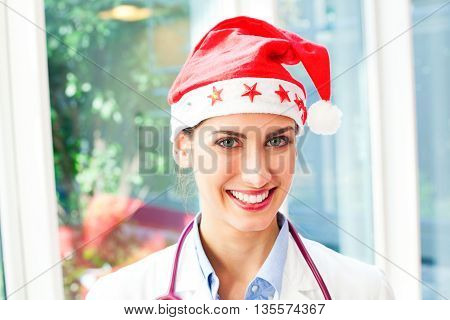 Portrait of happy female doctor wearing Santa hat. Beautiful young medical professional is smiling. She is with confident look on her face in hospital.