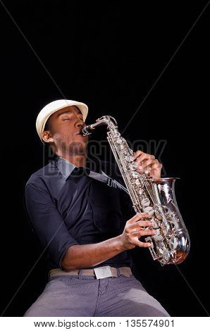 A nice view from below, black man is playing the saxophone. Professional hands with white hat.