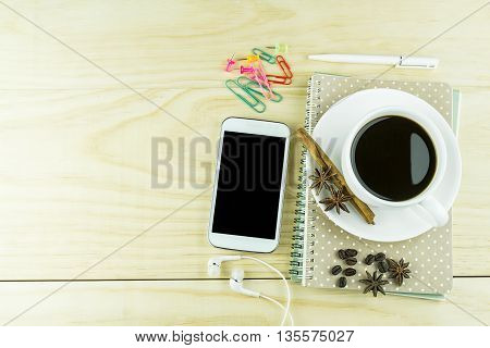 Smart phone coffeeglasses and book blank with white pen on wood table background. top view