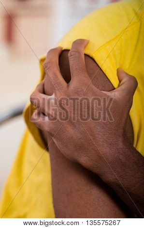 Close up of pain shoulder, man holding with his hand trying to make a massage.