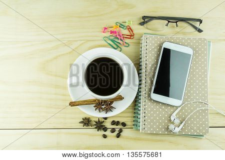 Smart phone coffeeglasses and note book on wood table background. Business concept