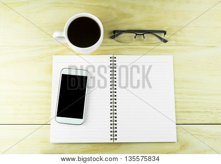 Smart phone coffeeglasses and book blank on wood table background. top view