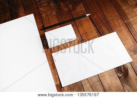 Close-up of blank stationery. Blank corporate identity template on vintage wooden table background. Blank letterhead business cards envelope and pencil.